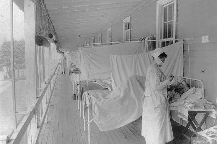 November 1918: A nurse takes a patient's pulse in the influenza ward of Walter Reed Hospital in Washington, D.C. | Harris & Ewing/Library of Congress