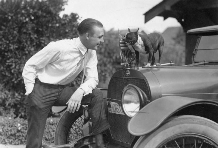 Actor Wallace Reid rests his foot on a car, possibly a McFarlan Six, as a small black and white dog watches. Reid died in 1923 at age 31. | Security Pacific National Bank Photo Collection/Los Angeles Public Library Collection