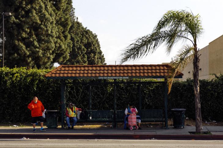 People social distance while waiting at a bus station in Huntington Park on April 2.   Chava Sanchez/LAist