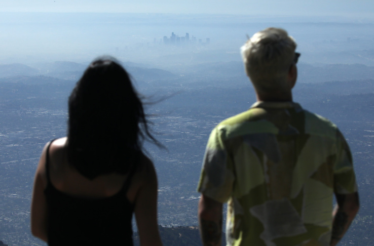 People take in the view with the buildings of downtown Los Angeles partially obscured at midday on November 5, 2019 as seen from Pasadena, California. | Mario Tama/Getty Images