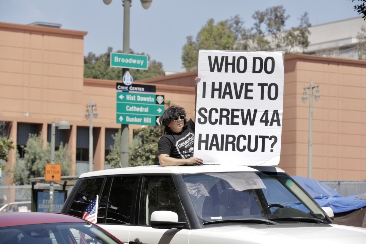 """A shaggy haired man holds a sign reading """"who do I have to screw 4a haircut"""" out of his cars sunroof. 