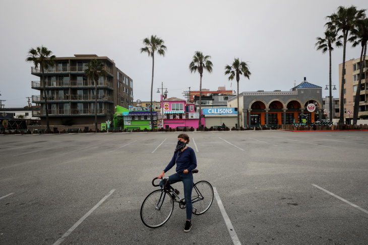 VENICE, CALIFORNIA - APRIL 26: A woman sits on her bike in a shuttered Venice Beach parking lot, which remains closed under stay-at-home orders amid the coronavirus pandemic. | (Photo by Mario Tama/Getty Images)