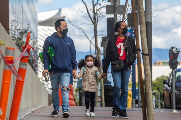A family walks wearing masks in downtown Los Angeles on March 22, 2020, during the coronavirus outbreak.   Apu Gomes/AFP/Getty Images