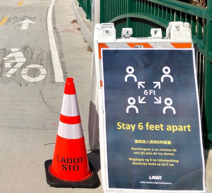 """""""Stay 6 feet apart"""" sign next to a traffic cone on a bike lane   Courtesy LADOT"""