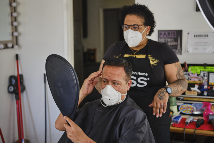 Carmelle and Eric review the results of his haircut inside Carmelle's Compton home. | Chava Sanchez/LAist