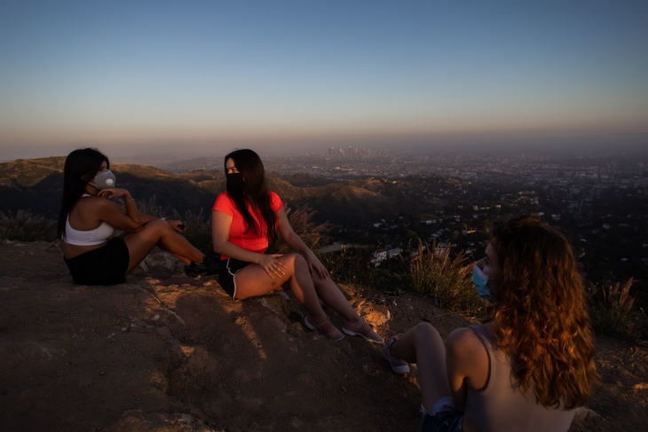 Bianca Freitas (L), Mayara Sonego (C) and Aurore (last name not given) (R) wear face masks while watching the sunset from Griffith Park on May 24, 2020.   (Apu Gomes/AFP via Getty Images) (APU GOMES/AFP via Getty Images)