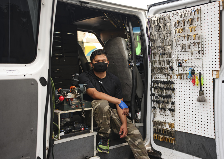 Juan Constantino, who attends the Communications & Technology school at the Diego Rivera Learning Complex in South L.A., poses in the mobile auto repair and locksmith shop where he works. | Chava Sanchez/LAist