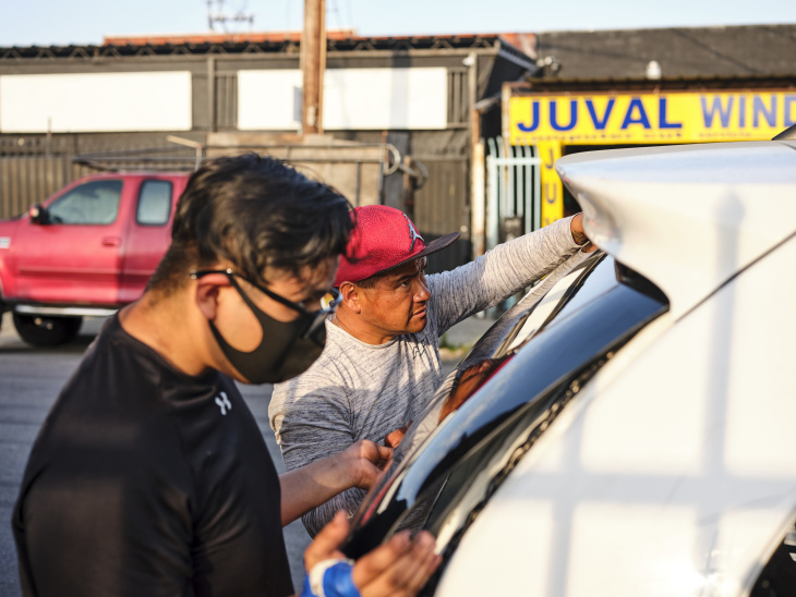 """Juan Constantino and his brother's dad replace a minivan's smashed-in rear windshield. """"Any little thing you can do to your car, we can do,"""" Juan said of the business. 