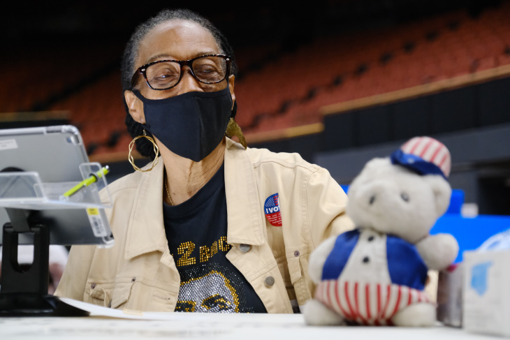 Ernestine Lindsay, poll worker for the last 16 years, brings her own stuffed bear to the vote center at the Forum in Inglewood. | Al Kamalizad for LAist