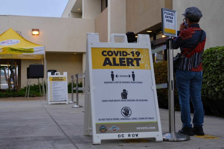 A person waits in line to vote at the O.C. Registrar. | Chava Sanchez/LAist