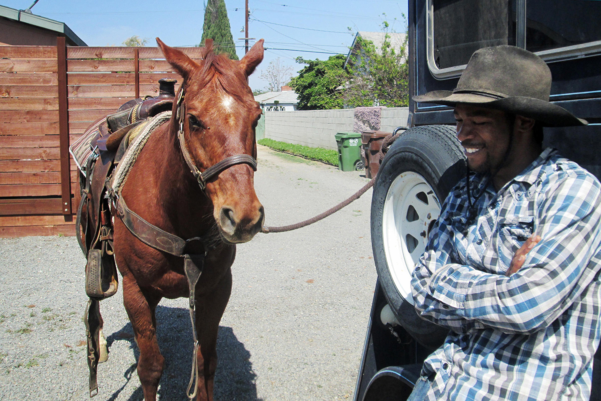 Richland Farms residen Derrik Jennings gets one of his horses ready to teach Compton kids all about horse bridles.  | Courtesy of Angel City Press