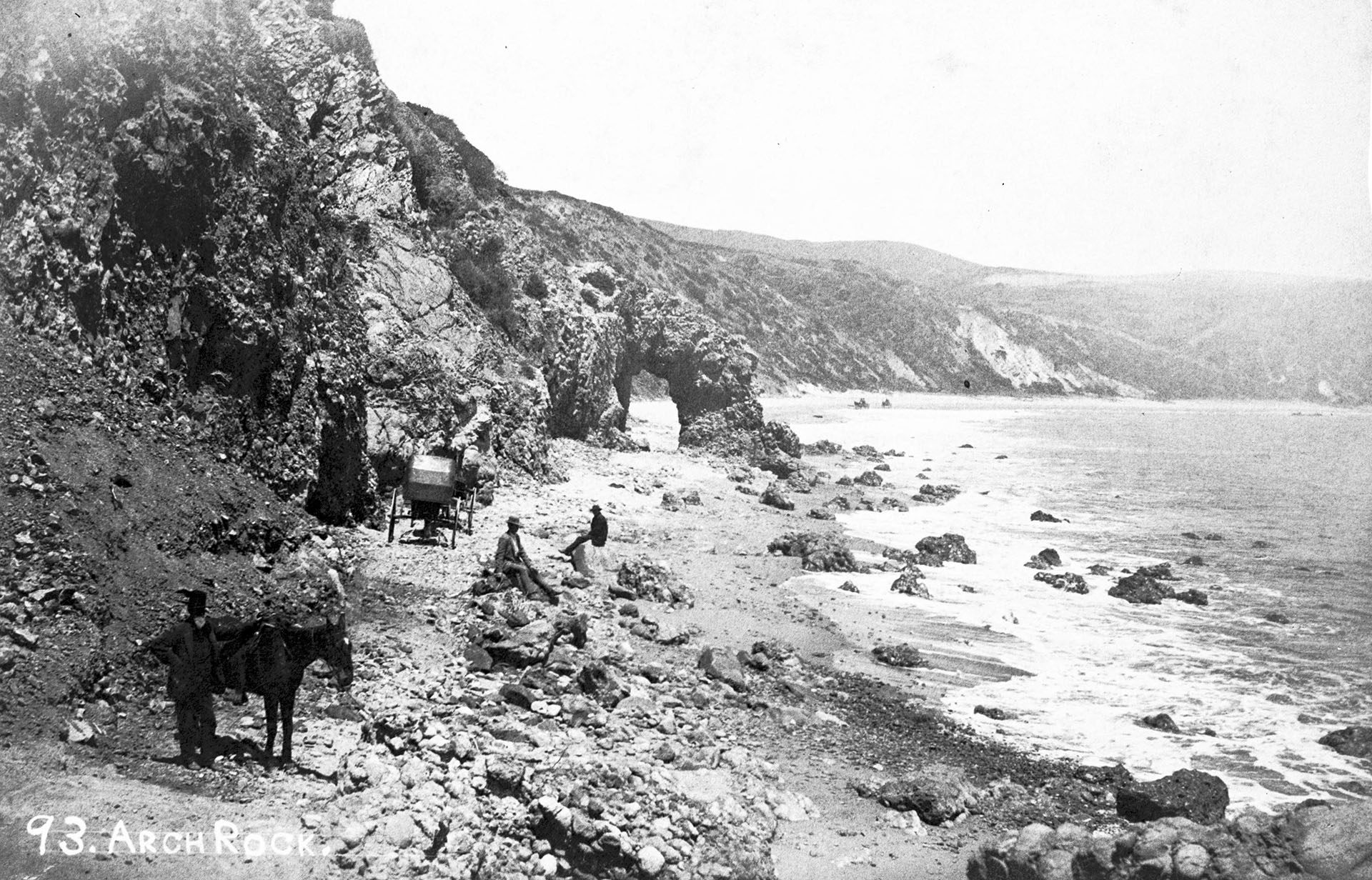 A view of Arch Rock in Santa Monica, showing a group of men posing along the rocks nearby, ca.1880