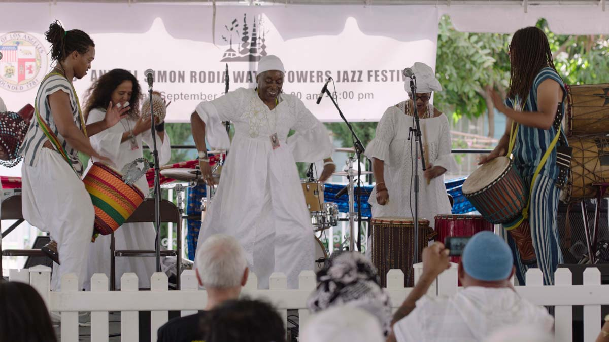 """A group of performers dance and drum at the Day of the Drum Festival at the Watts Towers Arts Center. 