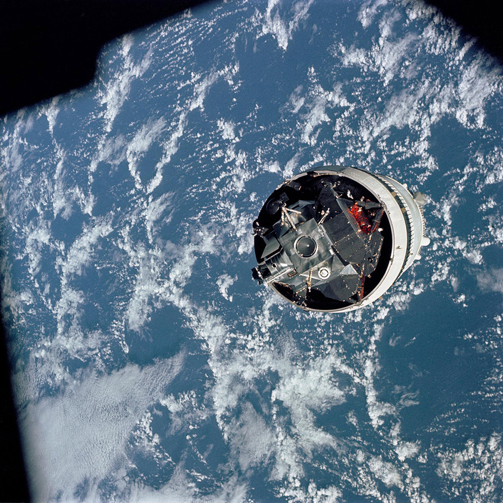 """Grumman's Lunar Module (LM) 3 """"Spider,"""" still attached to the Saturn V third stage (McDonnell Douglas' S-IVB), is photographed from the Command/Service Module (CSM) """"Gumdrop"""" on the first day of the Apollo 9 Earth-orbital mission. 