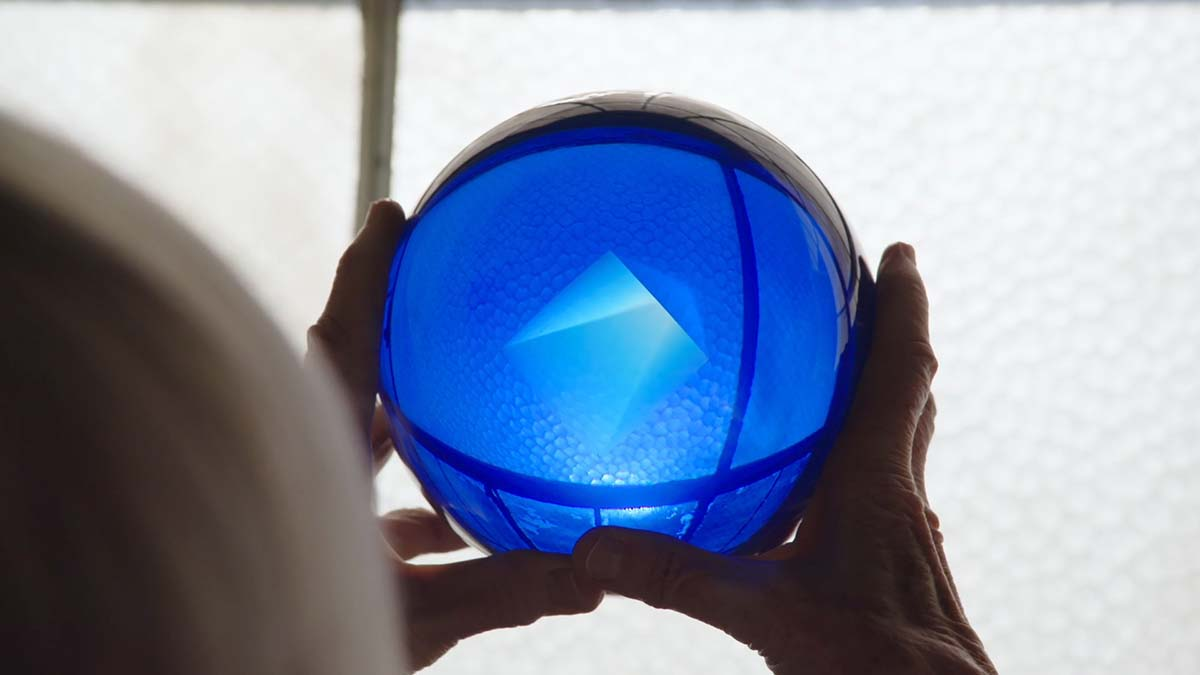 "Helen Pashgian holding up one of her blue spheres. Her work is a part of the Light and Space movement | Still from ""Light & Space"" ab s11"