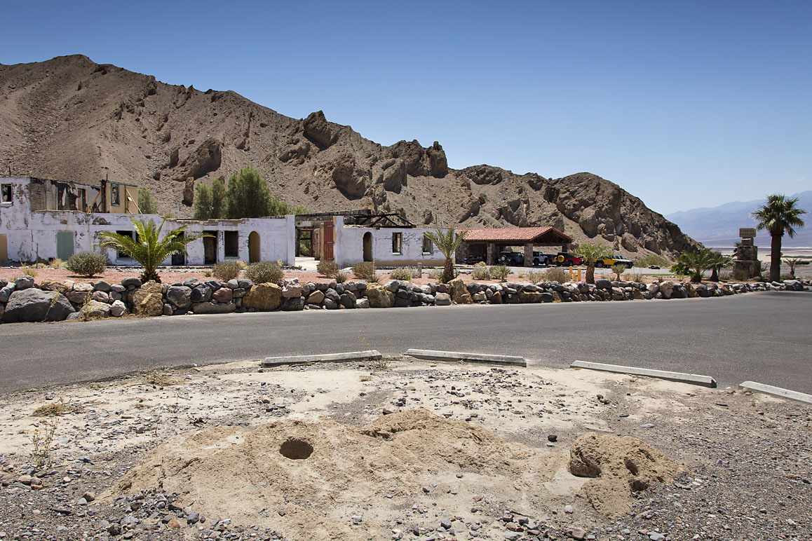Grinding Rock, an ancient Timbisha mesquite grinding site pictured in the foreground at Furnace Creek Inn's lower parking lot. In recent years part of the remaining rock artifact washed away during a flash flood.