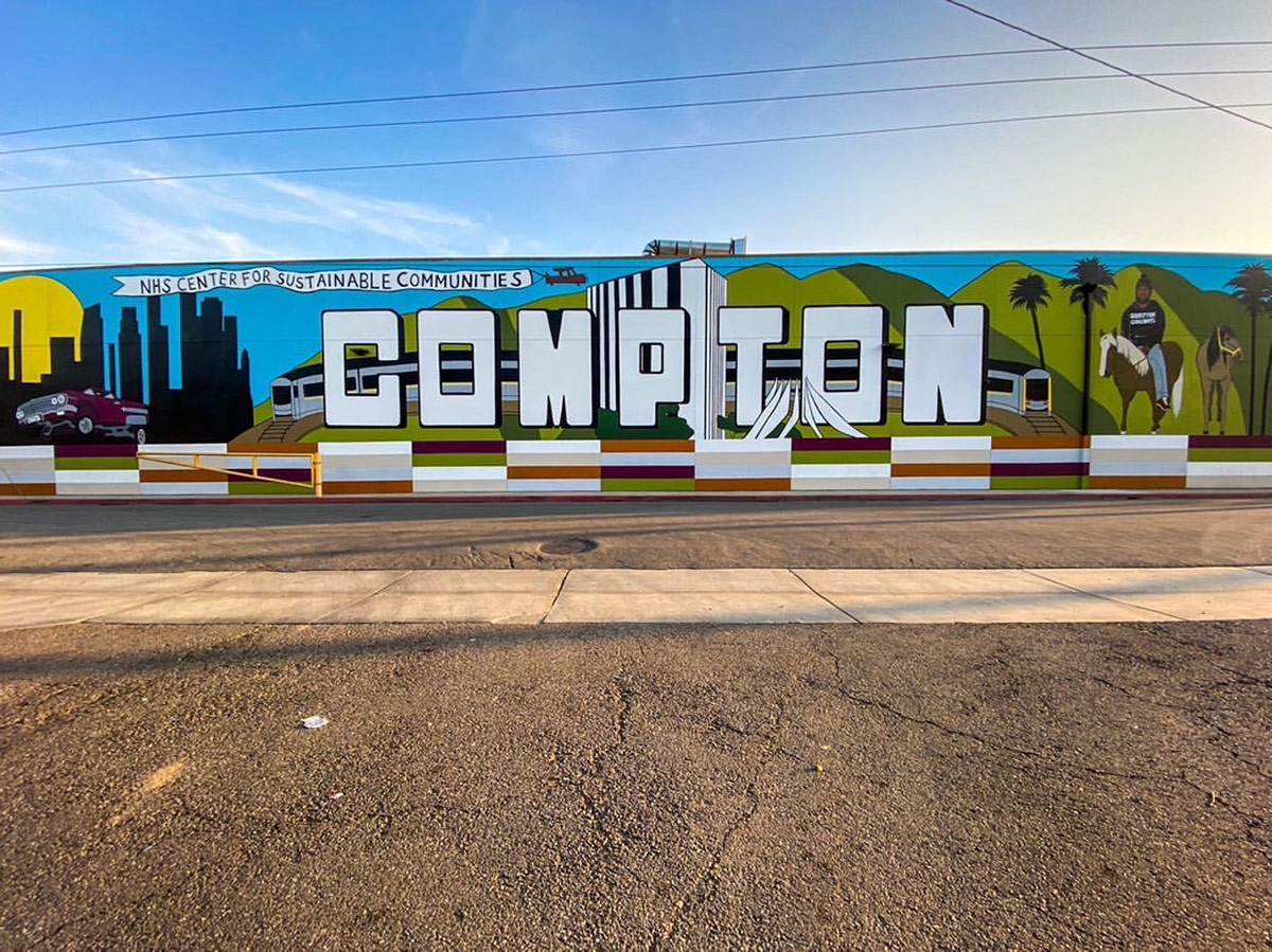 """The recent """"Compton"""" mural painted by local artists Anthony Pittman and Mel Depaz evokes Pinkney's legacy of murals that reflect the community's culture and pride. 