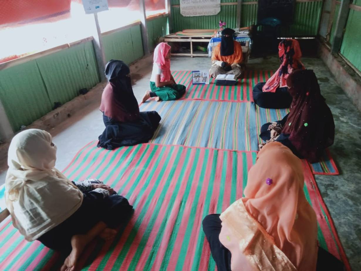 A woman in a burka sits down on the floor as she speaks to several other woman who are dressed and seated in the same way.