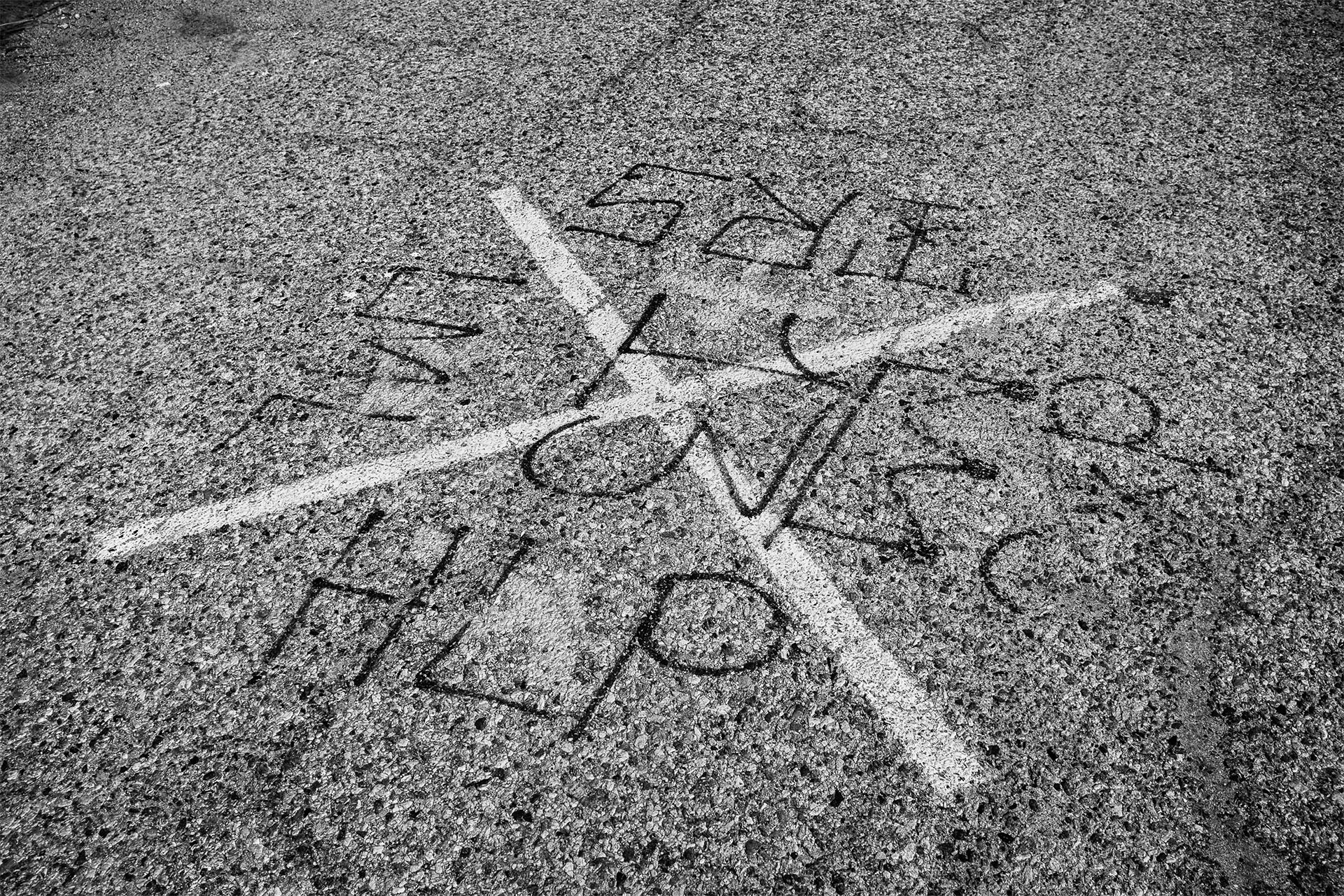 Tags on the ground at the Bowtie signify gang-related activity in the area | Photo by Bear Guerra