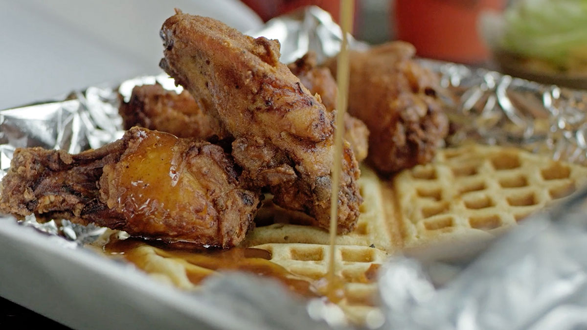 "Syrup drizzling over chicken and waffles. | Still from ""Broken Bread"""