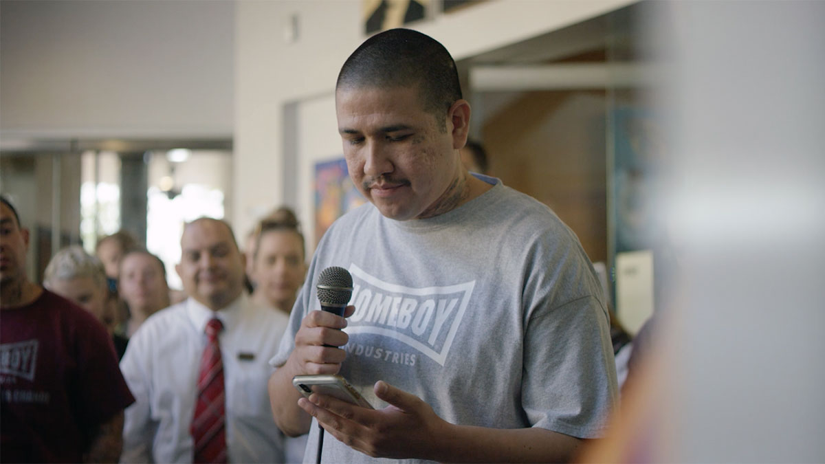 "Homeboy Industries member reads inspirational quote to the group. | Still from ""Broken Bread"""