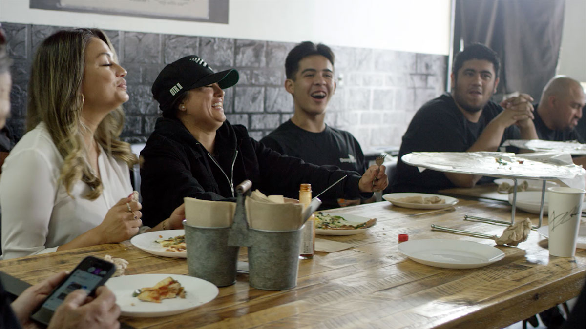 "Mar Diego of Dough Girl shares a meal with her employees and business partner. | Still from ""Broken Bread"""
