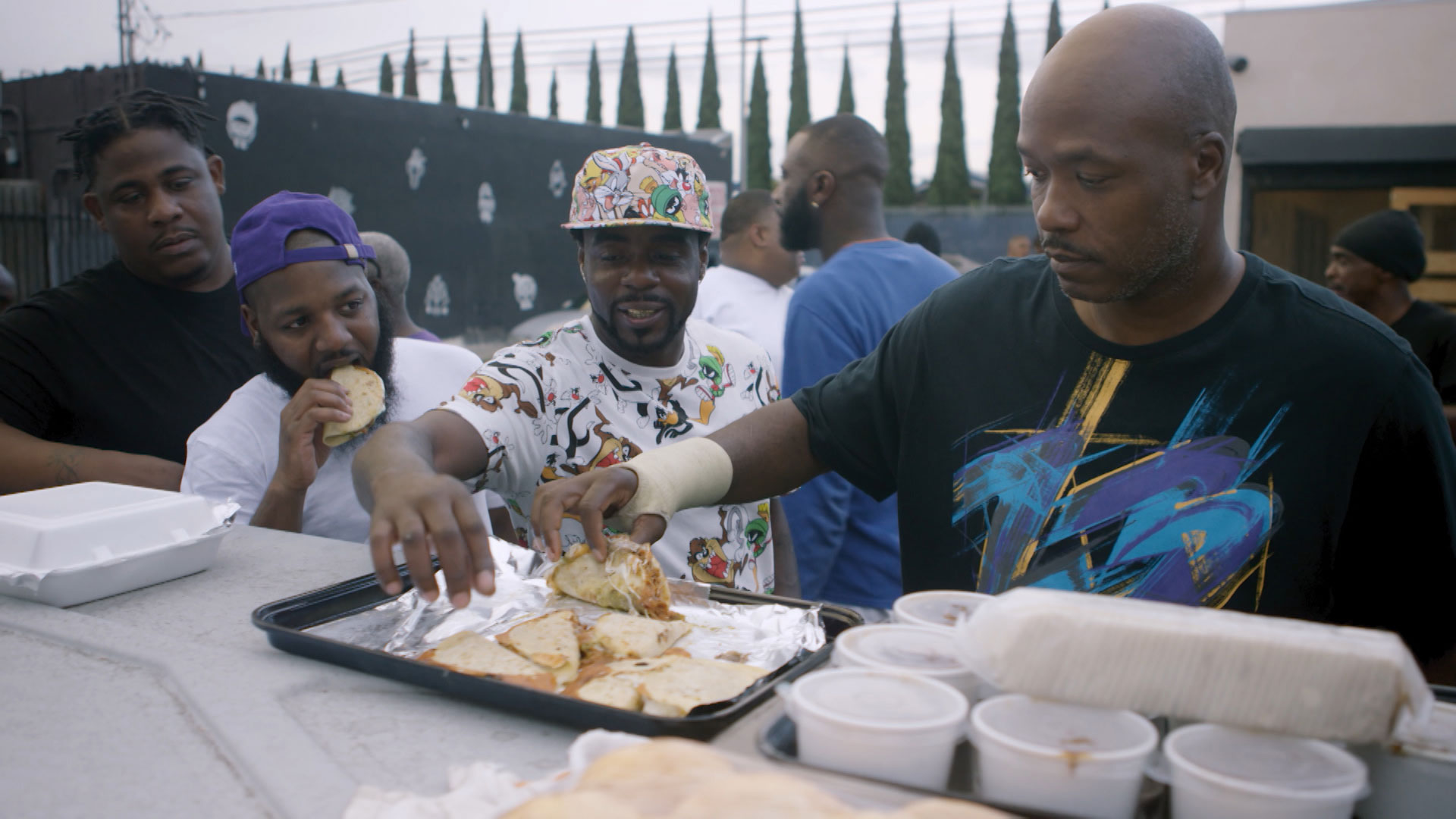 "Community members celebrate ""Hood Day"" eating turkey tacos at Locol. 