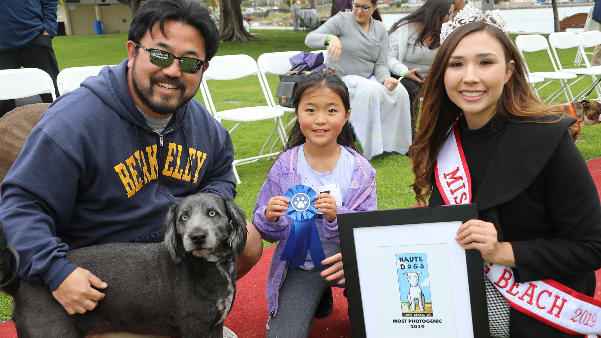 Man, child, and beauty queen pose with award-winning gray dog