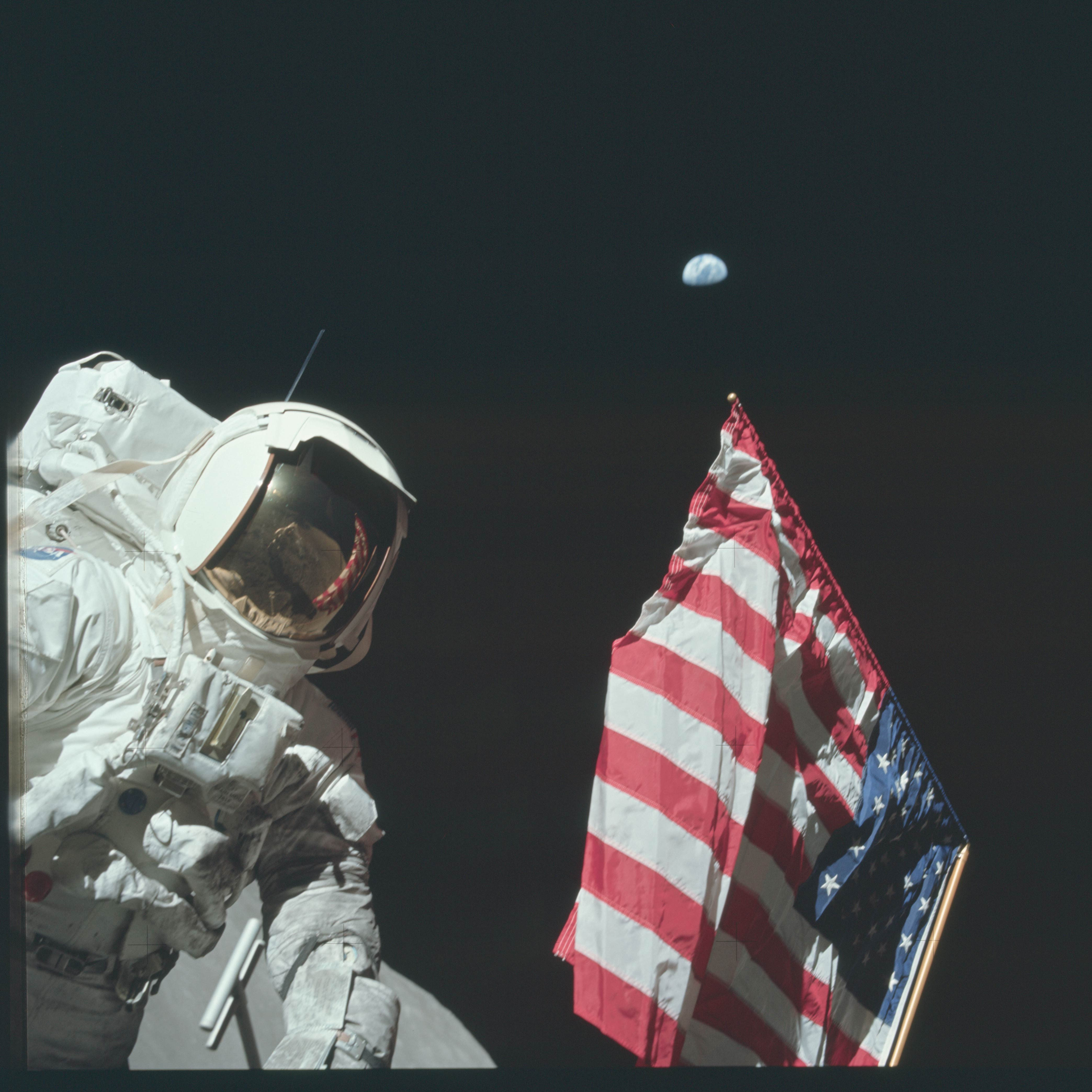 "From episode three: ""A Space Odyssey"" Apollo 11 astronaut Buzz Aldrin plants the flag with planet Earth above, c. 1969. Courtesy NASA"