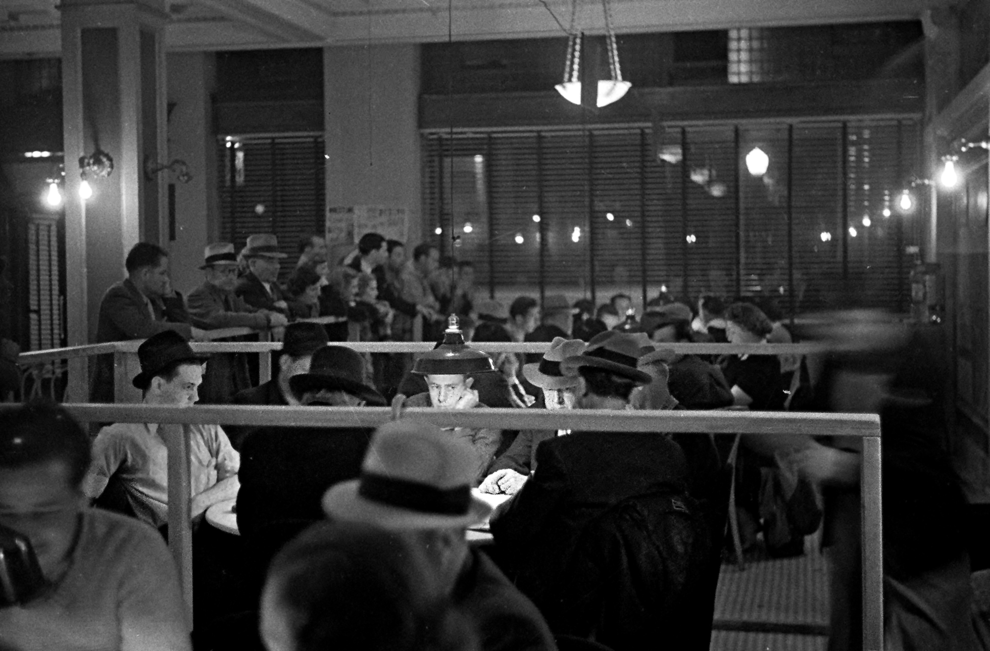 Gamblers playing cards, 1937. While other players wait for a seat, poker players watch the deal with various levels of interest.
