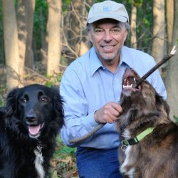 Picture of Carl Safina with a black- and brown-haired dogs.