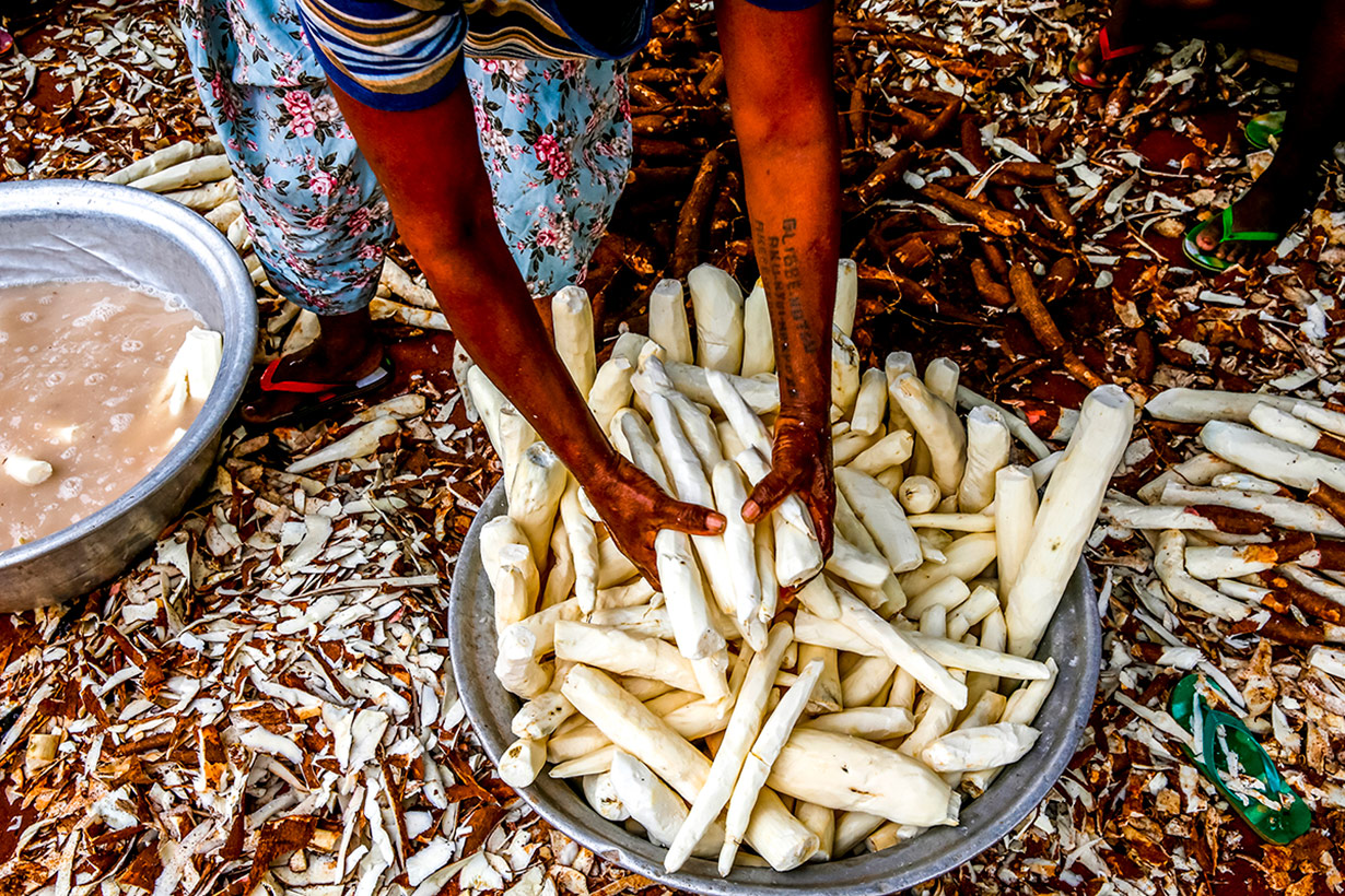 A woman peels cassava on the outskirts of Lomé, Togo. | Philippe Lissac / Godong / Getty Images