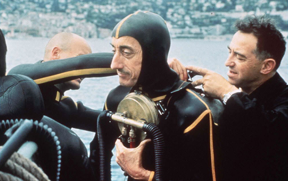 Members of Jacques Cousteau's team readies the famed explorer for a dive