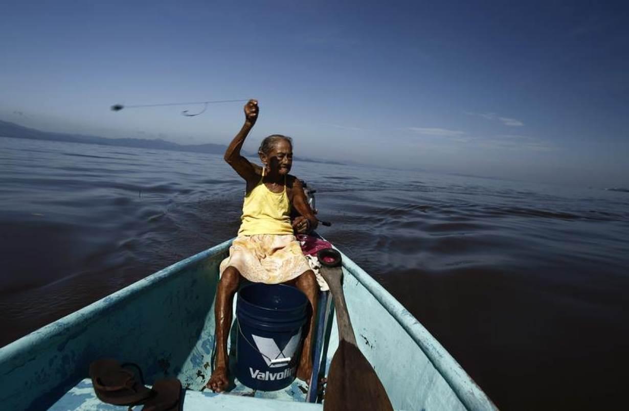 FILE PHOTO: Cecilia Villegas, 77, throws a fishing line along the sea of the Pacific coast of Cano Ciego Island near Puntarenas city October 3, 2012.   REUTERS/Juan Carlos Ulate