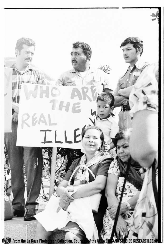 CSRC_LaRaza_B10F4C2_PA_022  Man holds sign during Centro de Accion Social Autonomo (CASA) march in front of the California State Building | Pedro Arias, La Raza photograph collection. Courtesy of UCLA Chicano Studies Research Center