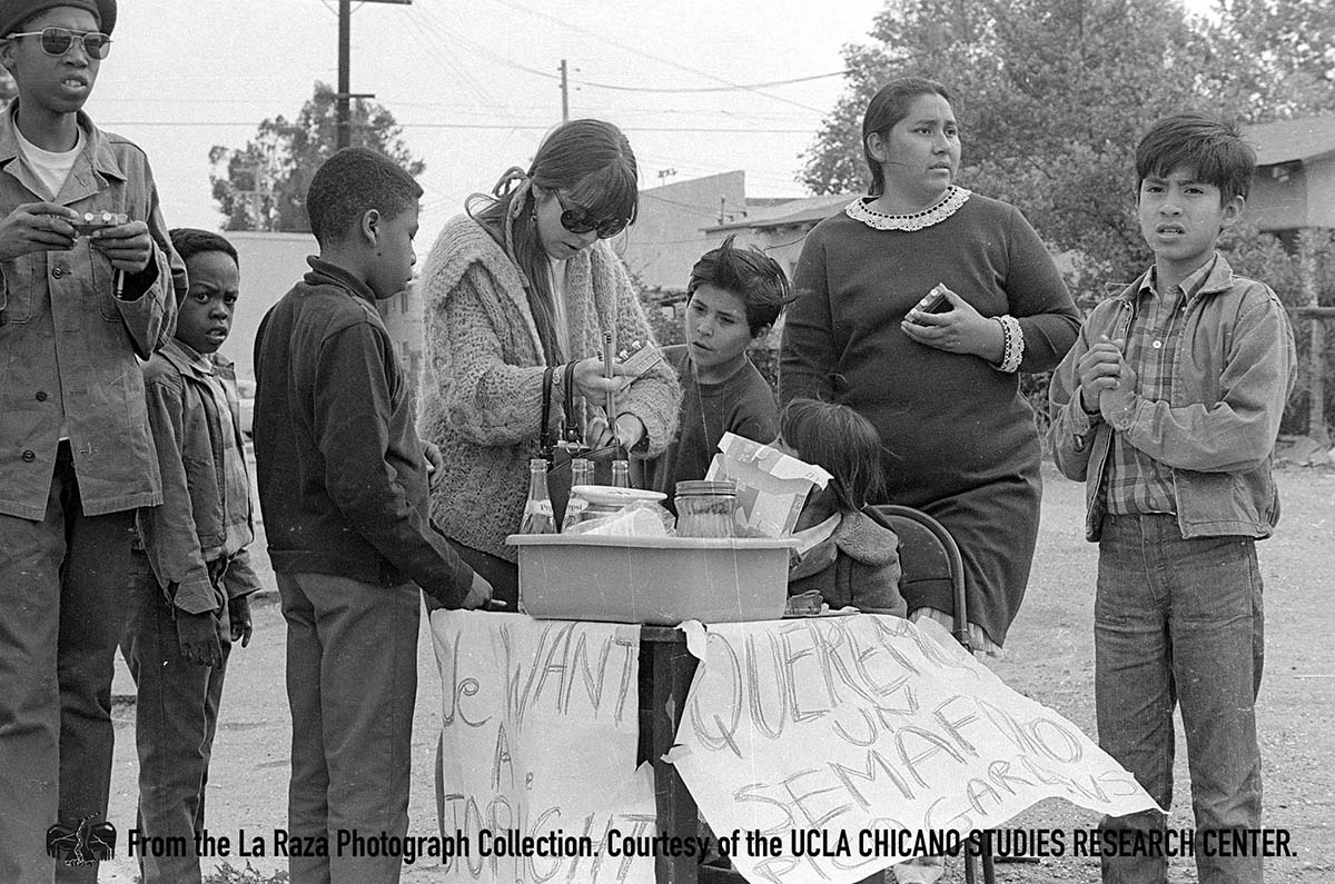 CSRC_LaRaza_B12F16S4_N013 Conchita Thronton with a group at a Pico Gardens and Aliso Village Traffic Light Demonstration | La Raza photograph collection. Courtesy of UCLA Chicano Studies Research Center