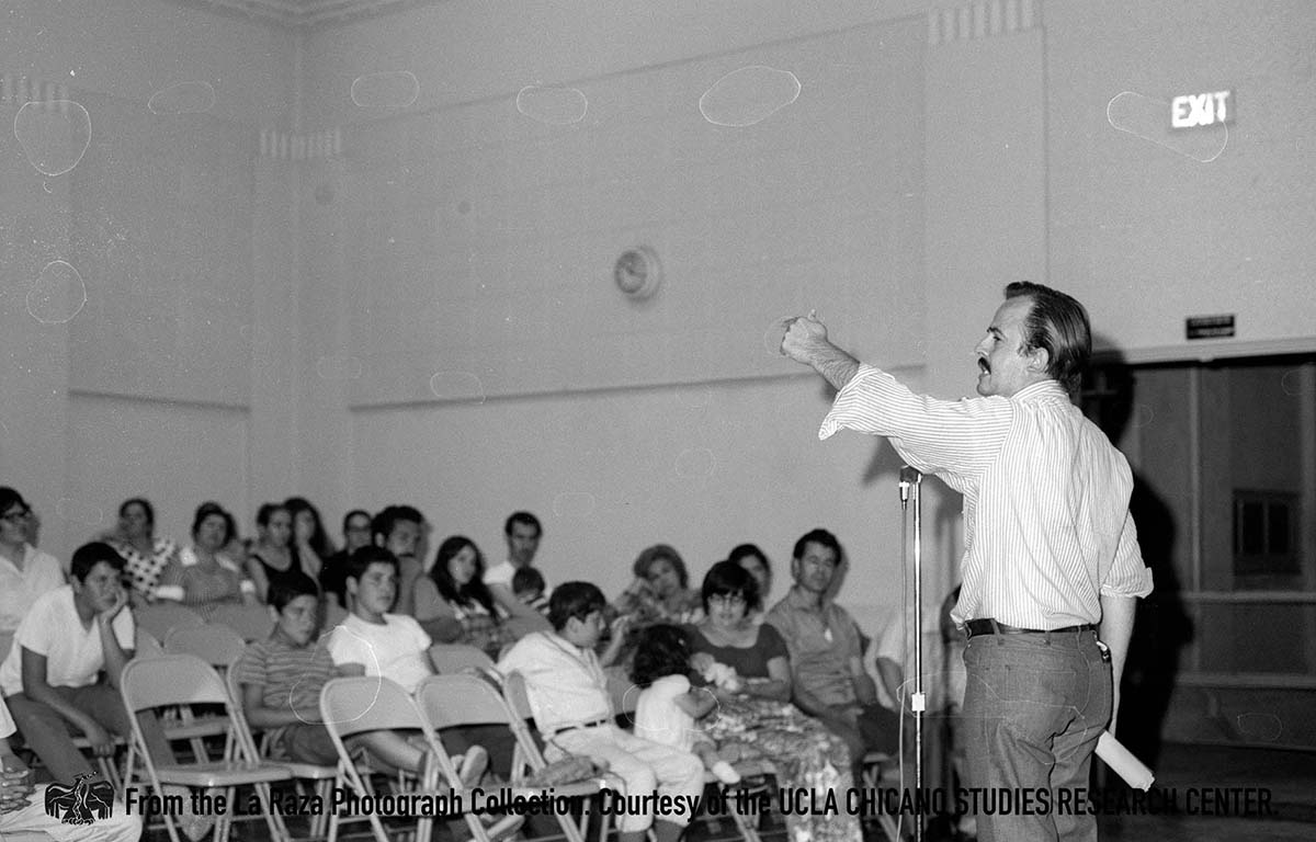 CSRC_LaRaza_B12F26S3_N010 Raul Ruiz speaks at a La Raza Unida meeting | La Raza photograph collection. Courtesy of UCLA Chicano Studies Research Center