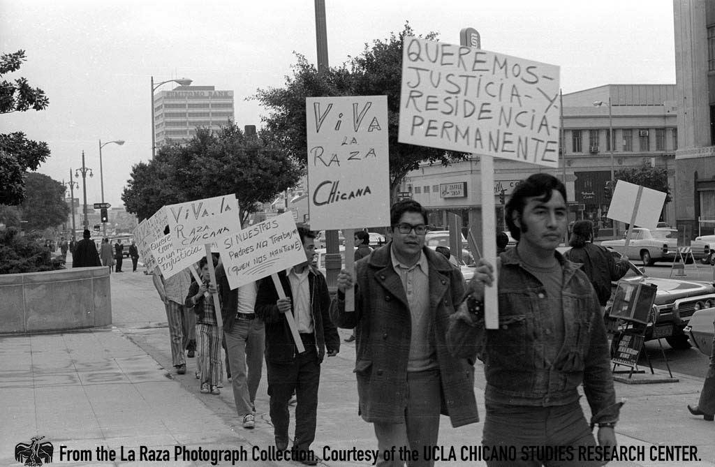 CSRC_LaRaza_B13F4S2_N003 People carry protest signs outside state building during a Center for Autonomous Social Action demonstration | Pedro Arias, La Raza photograph collection. Courtesy of UCLA Chicano Studies Research Center