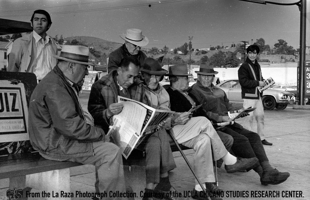 CSRC_LaRaza_B13F7S1_N002 A group of men reading a newspaper promoting Raul Ruiz as the La Raza Unida Party candidate for California's 48th Assembly District | Manuel Barrera, Jr. La Raza photograph collection. Courtesy of UCLA CSRC