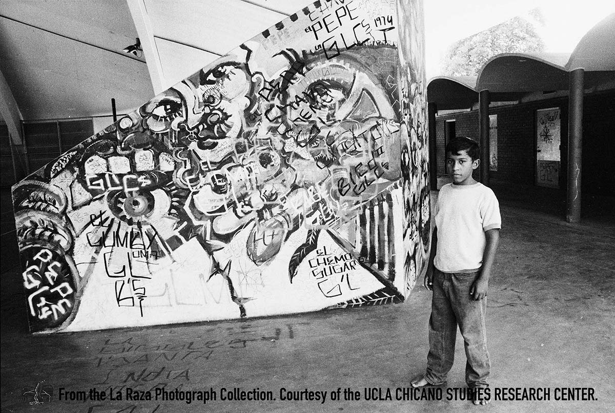 CSRC_LaRaza_B14F11S3_N034 Boy stands next to mural on bleachers in City Terrace | Manuel Barrera, Jr., La Raza photograph collection. Courtesy of UCLA Chicano Studies Research Center