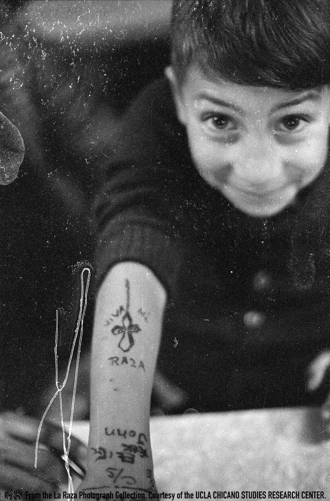 "CSRC_LaRaza_B14F3S1_N035 Child holds out his arm inside a restaurant with the words ""Viva mi raza."" 