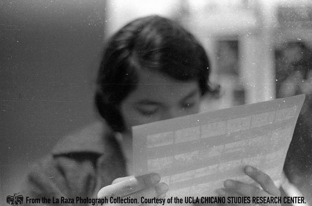 CSRC_LaRaza_B14F3S1_N044 Person views contact sheet inside the Chicano Student Movement newspaper office | La Raza photograph collection. Courtesy of UCLA Chicano Studies Research Center