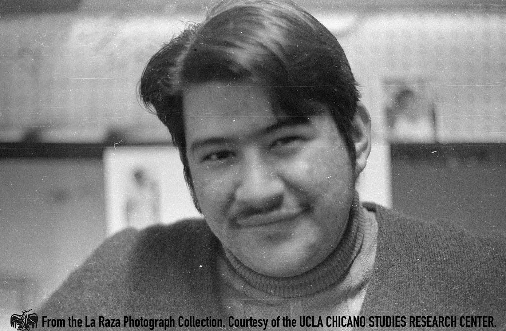 CSRC_LaRaza_B14F3S1_N060 Moctesuma Esparza poses at the Chicano Student Movement newspaper office | La Raza photograph collection. Courtesy of UCLA Chicano Studies Research Center