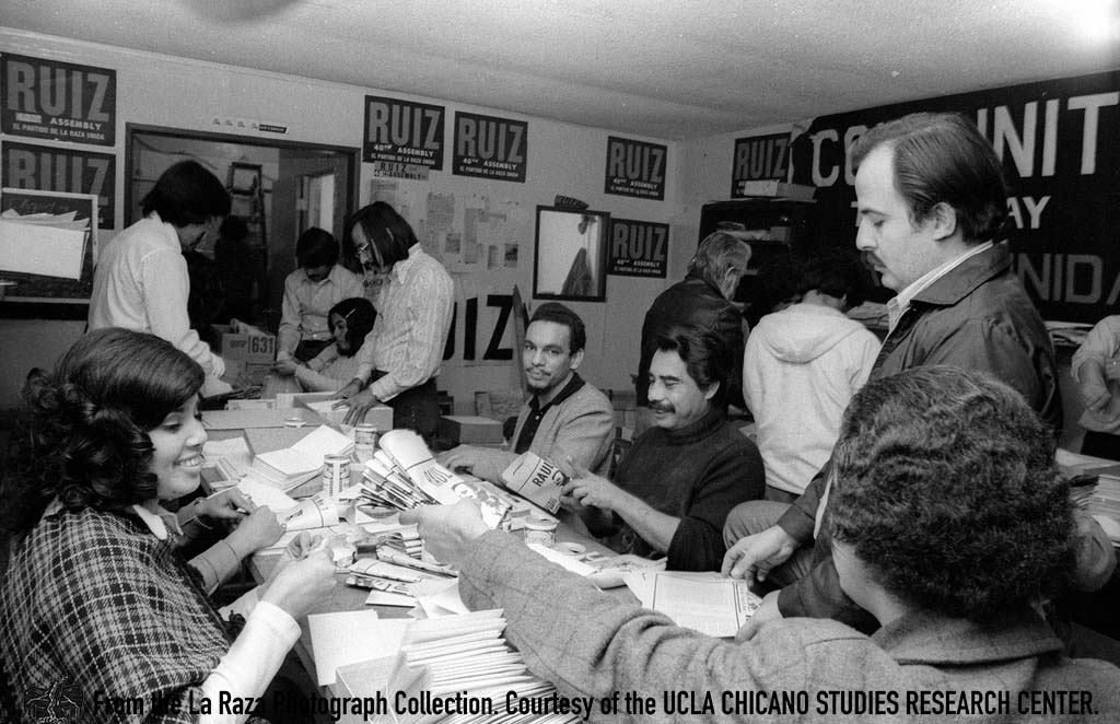 CSRC_LaRaza_B14F5S2_N001 Raul Ruiz and others fold campaign pamphlets | Manuel Barrera, Jr. La Raza photograph collection. Courtesy of UCLA Chicano Studies Research Center