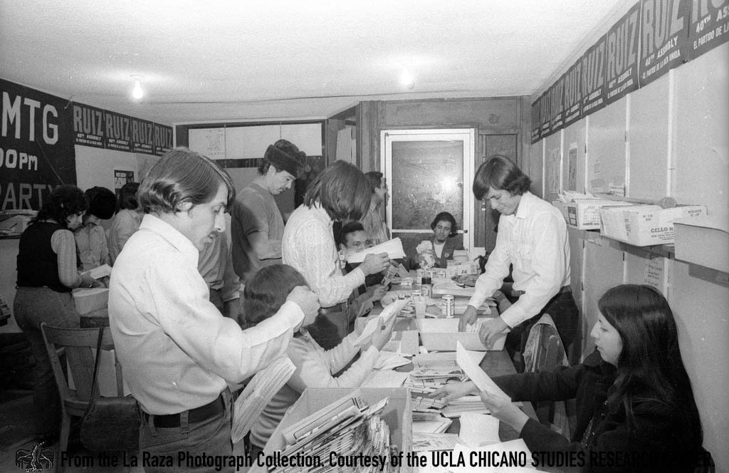 CSRC_LaRaza_B14F5S2_N003 A group of people, including Daniel Zapata, folds pamphlets for Raul Ruiz's campaign for California's 48th State Assembly district | Manuel Barrera, Jr., La Raza photograph collection. Courtesy of UCLA CSRC