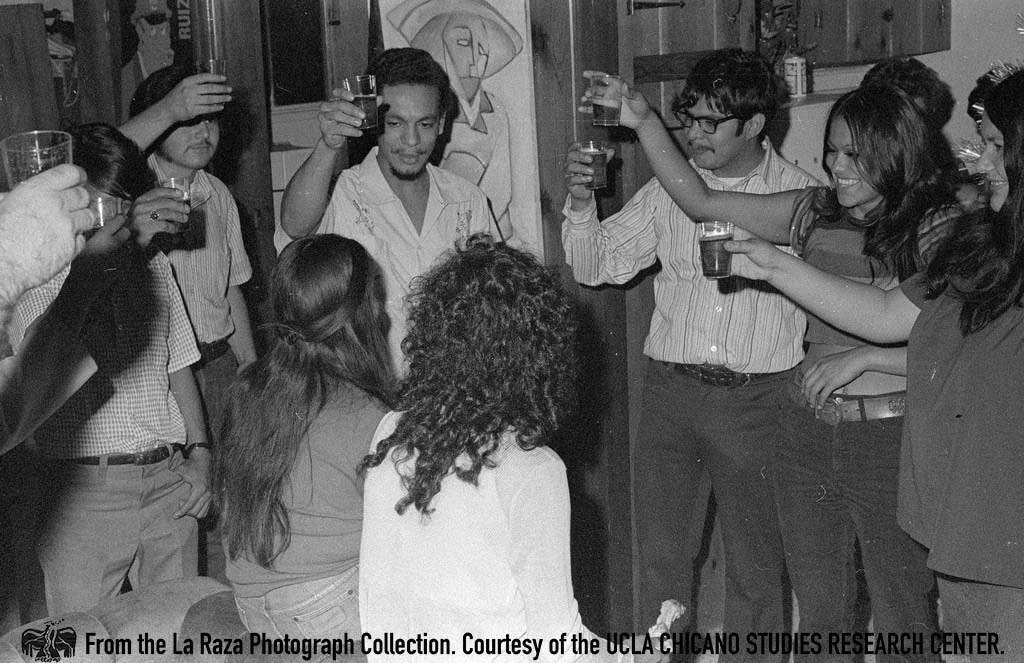 CSRC_LaRaza_B14F5S2_N010 Toasting during La Raza staff party | Manuel Barrera, Jr., La Raza photograph collection. Courtesy of UCLA Chicano Studies Research Center
