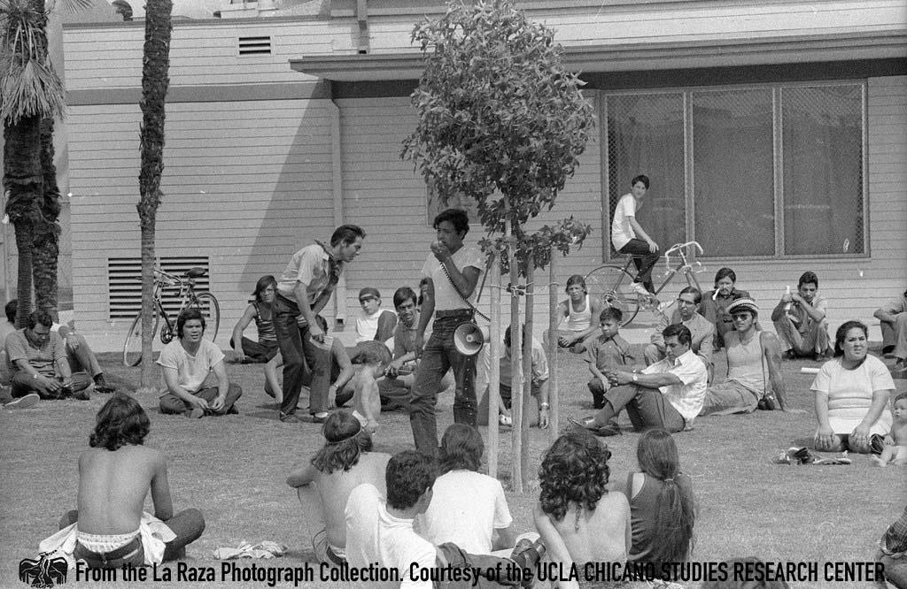 CSRC_LaRaza_B14F6S1_N013 Man speaks to a crowd at Chicano Moratorium anniversary | Patricia Borjon Lopez, La Raza photograph collection. Courtesy of UCLA Chicano Studies Research Center