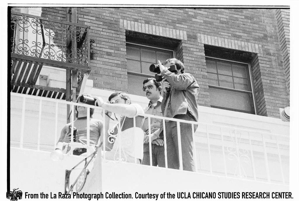 "CSRC_LaRaza_B15F14C1_Staff_005 Man photographs protesters at ""Dump Nixon"" march   Maria Marquez Sanchez, La Raza photograph collection. Courtesy of UCLA Chicano Studies Research Center"