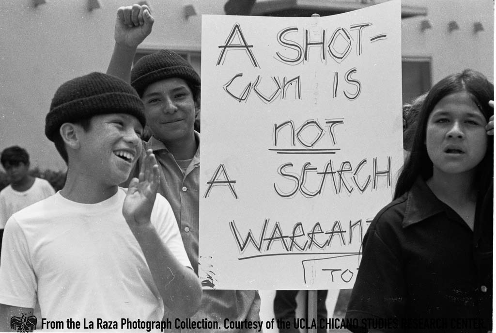 CSRC_LaRaza_B15F2C3_PB_022 A boy holds a sign during la Marcha por los Tres | Patricia Borjon Lopez, La Raza photograph collection. Courtesy of UCLA Chicano Studies Research Center