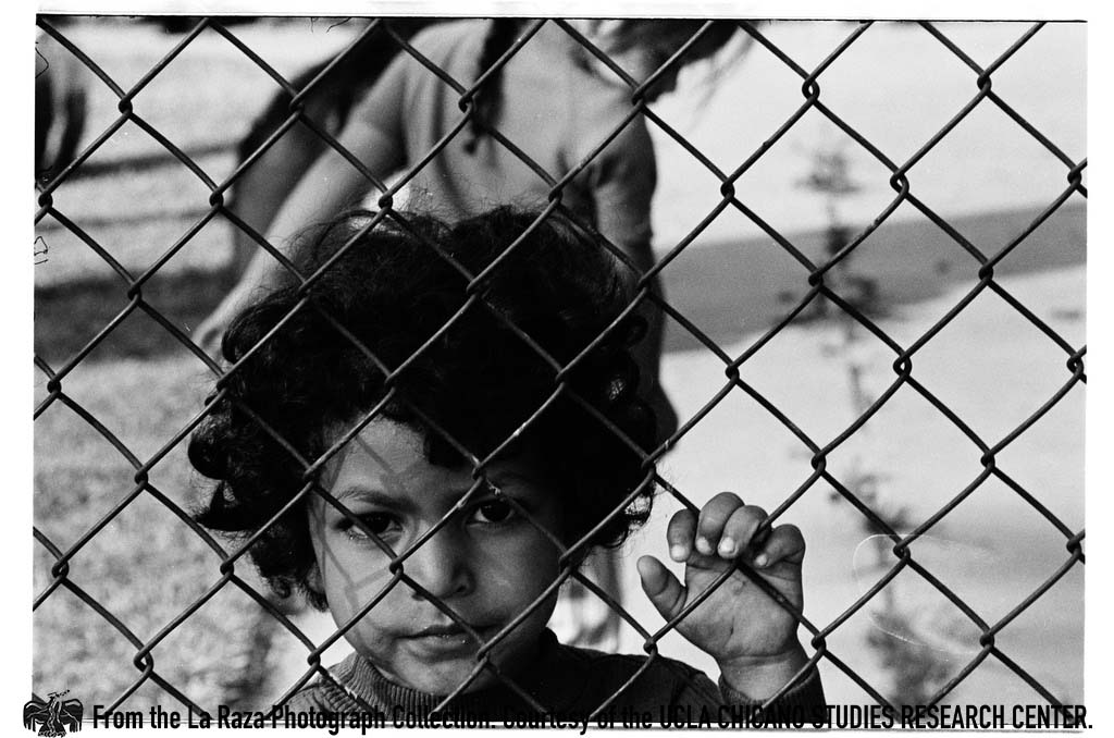 CSRC_LaRaza_B16F6C9_Staff_015 Young boy behind chainlink fence | La Raza photograph collection. Courtesy of UCLA Chicano Studies Research Center